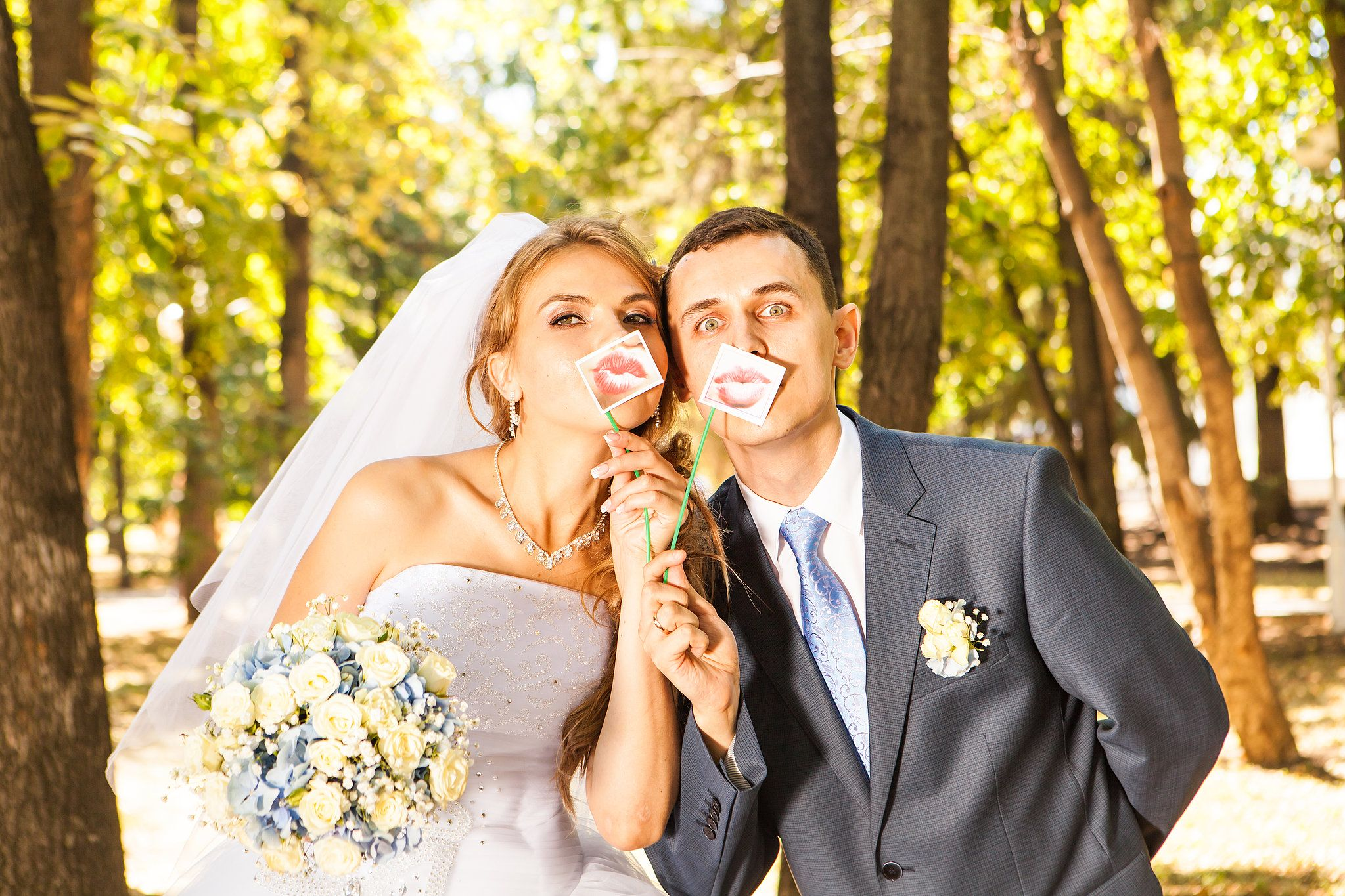 Wedding couple posing with stick lips, mask. Wedding accessories